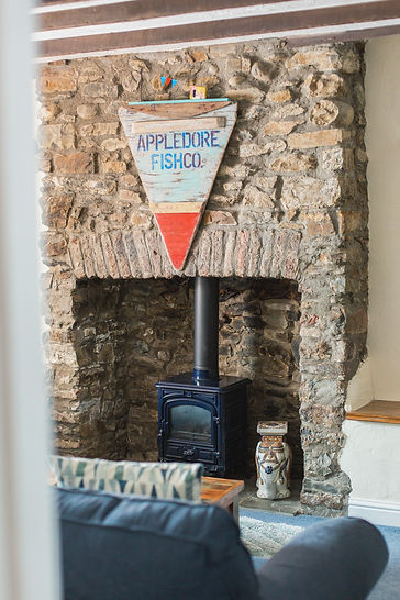 Large cob fireplace with fire and triangular wooden artwork hanging above reading Appledore Fish Co