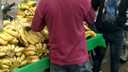 Fruit vendor distributing bananas to the needy