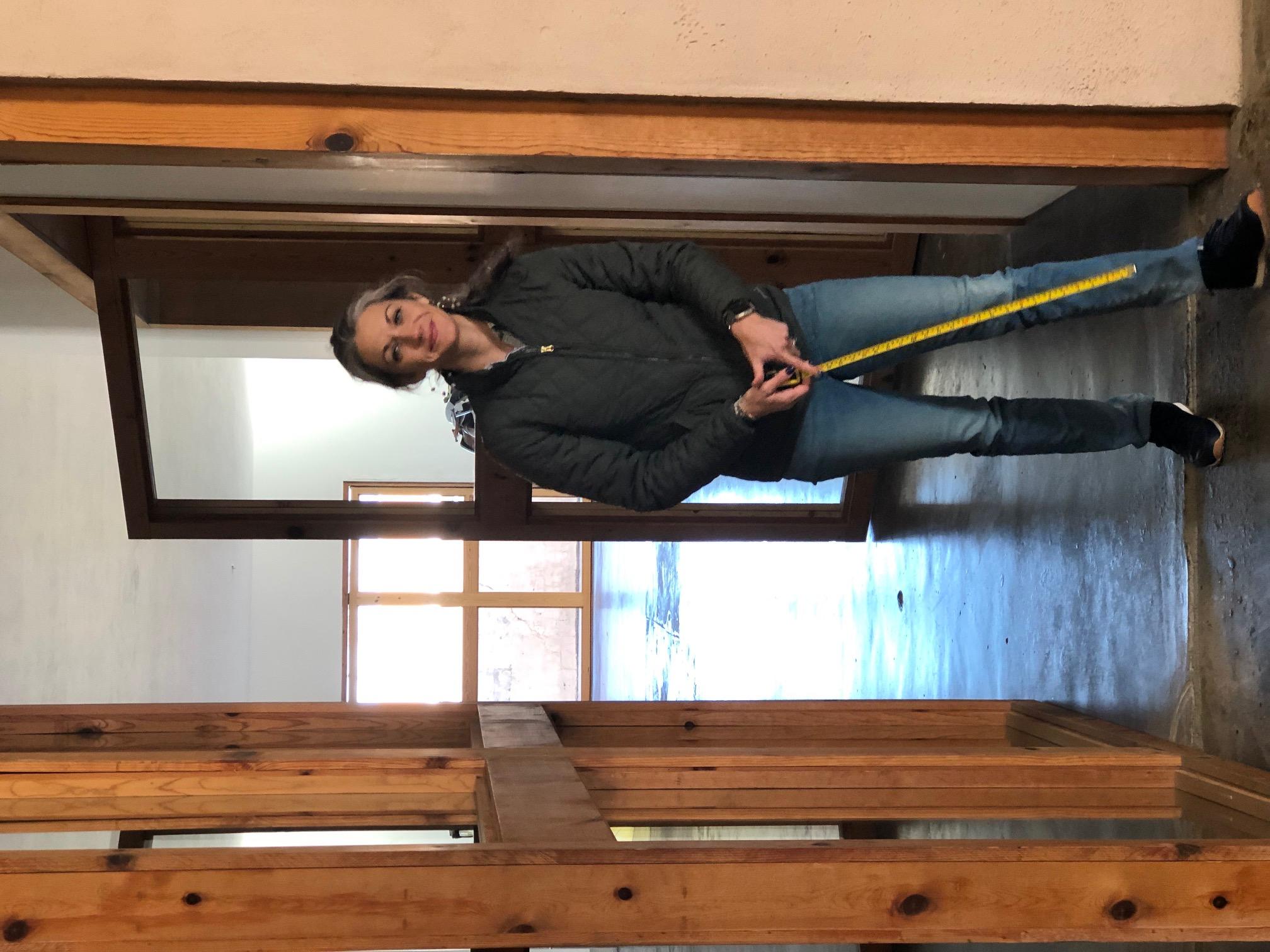 Elaine Andersen standing in doorway, holding a tape measure
