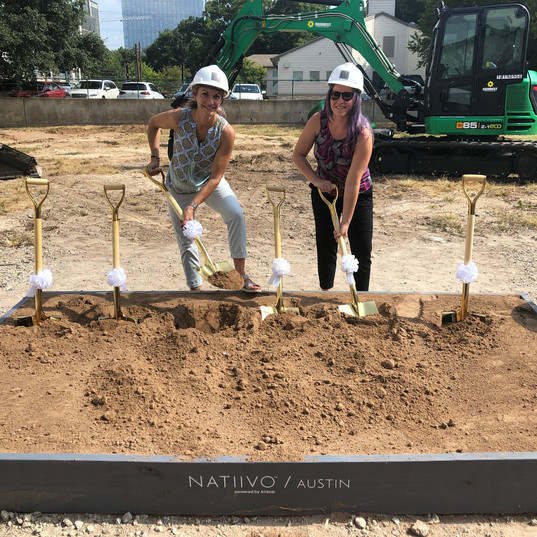 Two people in hard hats, digging gold shovels into dirt at a ground breaking