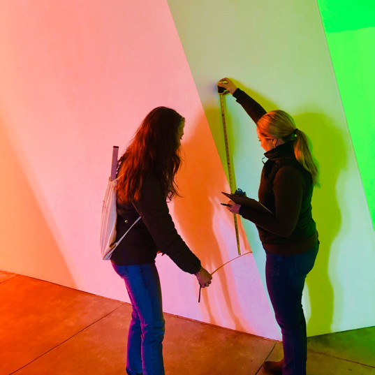 Two people inspecting art gallery, holding tape measure with bright lights