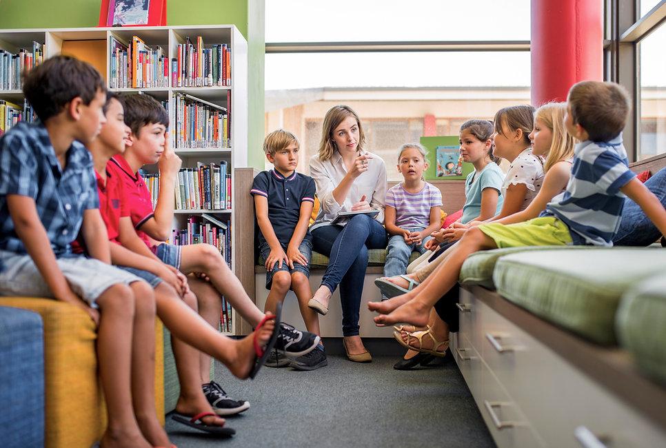 Professor e crianças na biblioteca