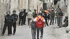 Palestinian school children walk past Israeli riot police during clashes with masked youth