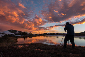 A student photographs sunset at a pond near Forest Canyon Pass, Rocky Mountain National Park, Colorado