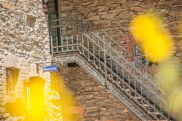 Gelungener Nachbau einer alten handwerklich gefertigten Außentreppe, die sich perfekt einpasst ins Gesamtambiente der Hofreite.