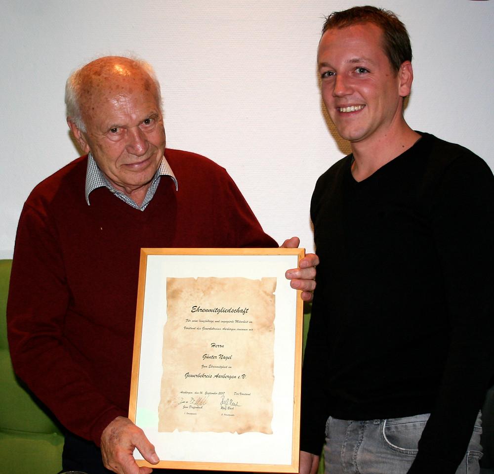 Günter Nagel (links) nimmt von Jens Diefenbach die Urkunde zur Ehrenmitgliedschaft beim Jubiläum des Gewerbekreises Aarbergen e.V. entgegen.