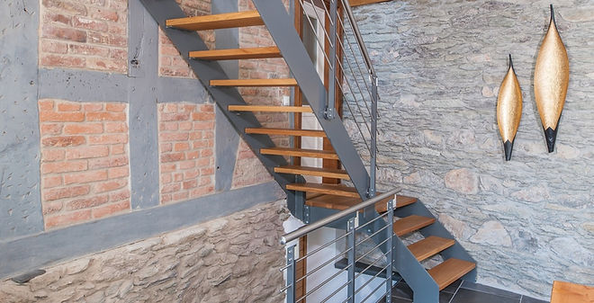 Diese luftige Stahltreppe mit Holzstufen und Relingstabgeländer passt in Farbe und Material perfekt zum Fachwerk. Durch die schlanke, offene Bauweise bleibt viel Leichtigkeit und Transparenz erhalten. Der Mix aus Stahl und Holz bei Treppenaufgängen in Fachwerkhäusern ist sehr beliebt.