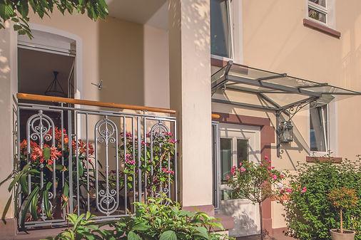 Stahlvordach mit Glas, Verbundsicherheitsglas mit Selbstreinigungseffekt, Balkongeländer mit massiven, gusseisernen Stäben mit Eichehandlauf