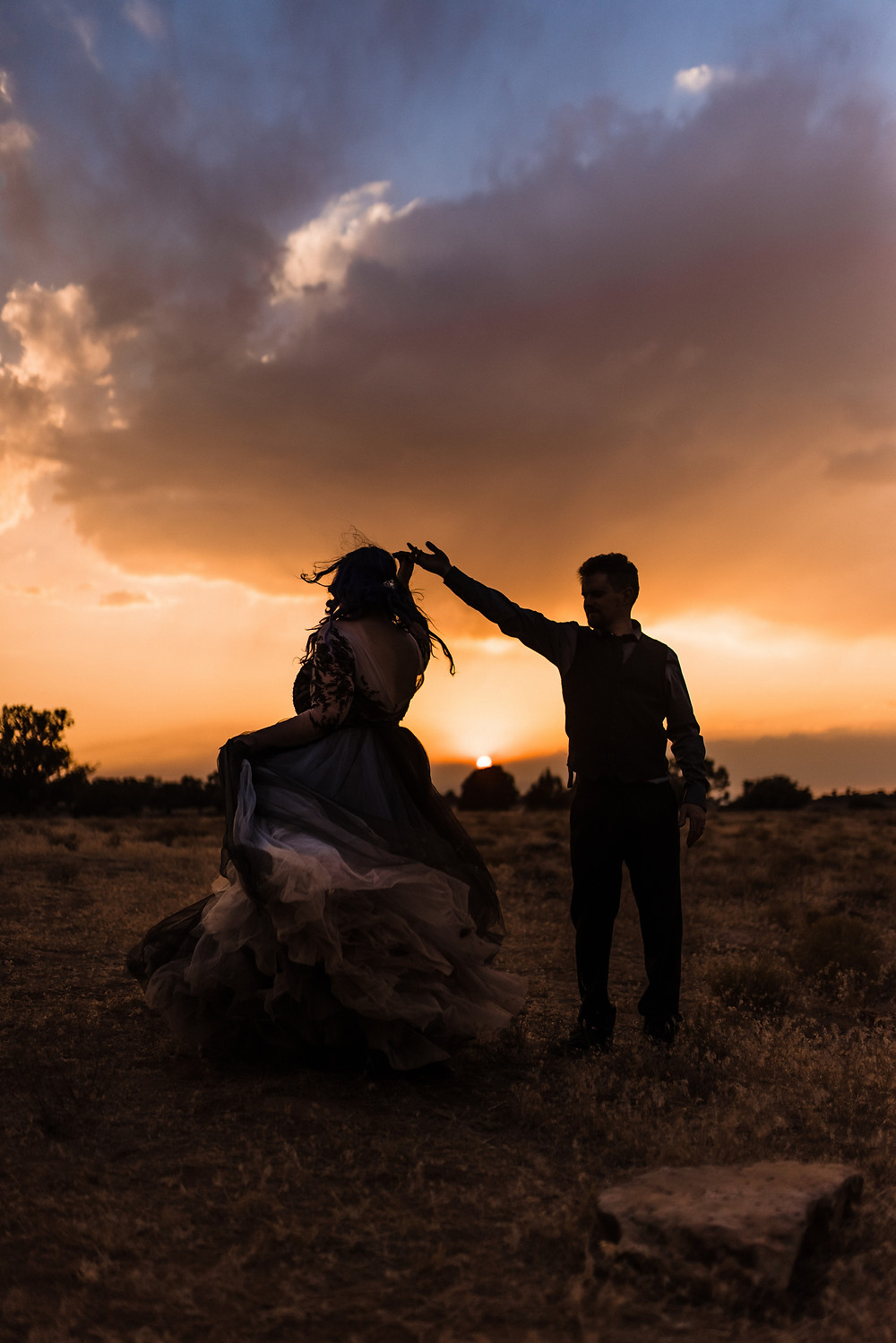 Newly wed couple dancing at Sunset after golden hour wedding photos in Southern Utah. #sunsetweddingphotos #weddingphotography #weddingdance #darksunset #couplephotos #justmarried #weddingplanner #eventplanner #utahweddingplanner #utahwedding