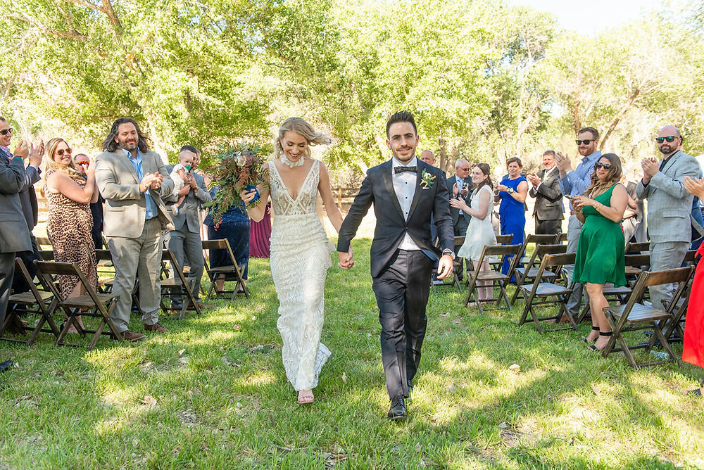 Just married couple walking down the aisle in Zion National Park to head towards cocktail hour and begin the night. #justmarried #cocktailhour #weddingdress #groomsuit #bridalbouquet #outdoorwedding #utahwedding #weddingday #weddingaisle #ceremony #ceremonyexit #grandexit