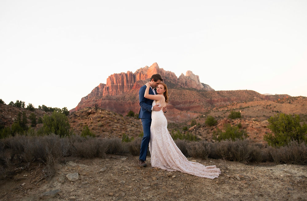 Bride and Groom Wedding photo in front of Zion National Park mountains hugging for an intimate photo after elopement with dress train flowing down rocks. #zionwedding #summerwedding #hotsummerwedding #beattheheat #zionnationalpark #eventplanner #weddingphoto #zionelopement #mountainwedding #destinationwedding #destinationelopement