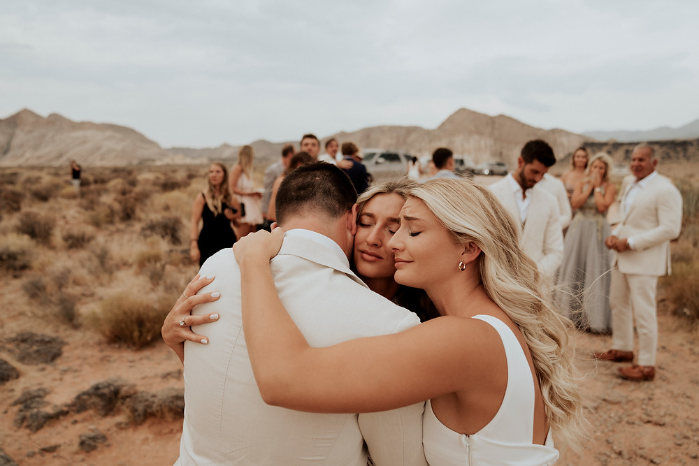 Brother and sister hug the just married bride after the ceremony for an emotional wedding photo. #weddingphoto #uniquewedding #bohowedding #outdoorwedding #destinationwedding #destinationelopement #weddingdress #whitewedding #whiteandcreamwedding #zionnationalpark