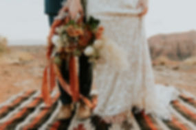 Boho elopement in southern utah near zion national park with a barefoot bride in a boho fringe and lace wedding dress on a striped rug holding a gorgeous desert bouquet with rust colored ribbon. Boho bridal shoot. southern utah wedding planner zion destination wedding planner zion elopement bride-to-be wedding planning in southern utah boho wedding dress bridal bouquet desert bridal bouquet in southern utah