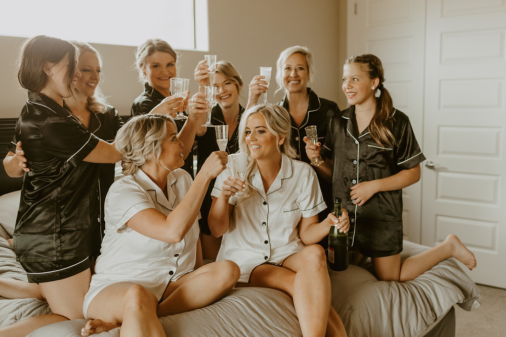 Same sex brides and all of their bridesmaids in matching silk pajamas making a toast and cheering with some champagne for their getting ready photos. #cheers #gettingreadyphotos #bridesmaids #matchingpajamas #weddinginspo #champagnetoast #weddingday #weddingplanner #utahwedding #bridepajamas