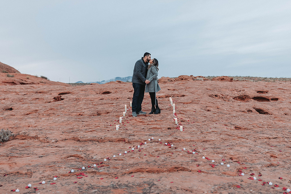 Newly engaged couple stopping their walk for a kiss in a walkway lit with candles and rose petals in the shape of a heart. #engagementphotos #weddingring #candlelitwalkway #utahengagement #utahwedding #weddingplanner #eventplanner #engagementcoordinator #redrockproposal #weddingring
