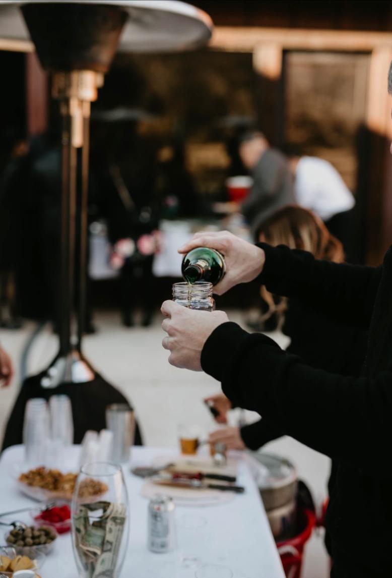 Bartender making a drink at a wedding on the Wedding day detail shot. #bartender #cocktail #cocktailhour #weddingdrinks #weddingbartender #maglbys #outdoorheater #weddingelopement #southernutahwedding #eventplanner #weddingplanner