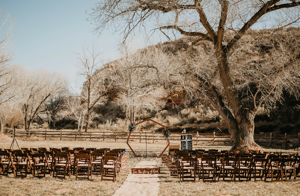 Ceremony Set up in Zion National Park with aisle and wedding arch shown under a large tree for shade. #weddingarch #ceremonyarch #woodenchairs #woodenceremonychairs #woodweddingchair #zionwedding #eventplanner #zionnationalparkwedding #outdoorwedding #weddingaisle #weddingday