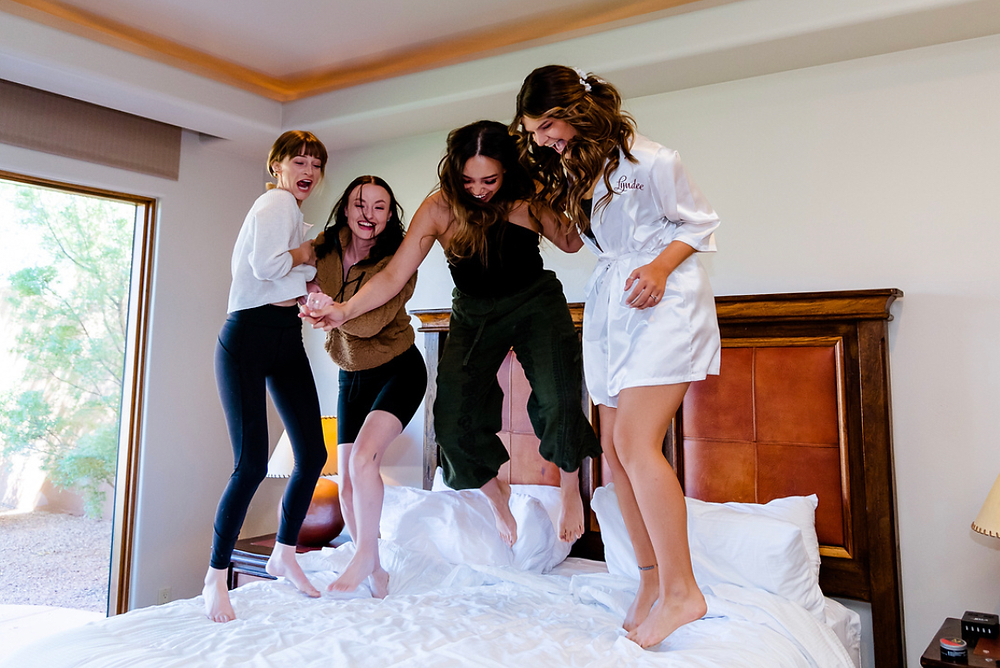 Bride and her bridesmaids jumping on the bed to get some wedding anxiety out during getting ready photos. #bridesmaids #weddinganxiety #weddingday #weddingnerves #bride #weddingplanner #eventplanner #utahwedding #weddinghair #weddingmakeup #weddingdayfun