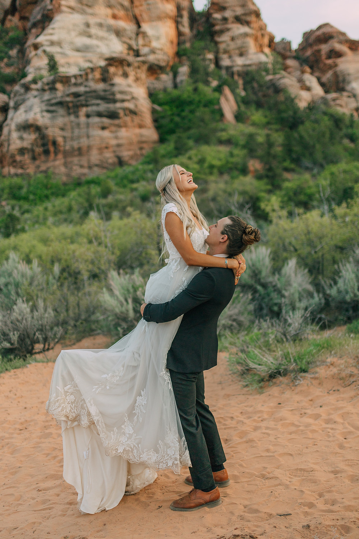 Bride and Groom dancing in the desert for their outdoor wedding in Southern Utah in their wedding dress and wedding suit. #bride #groom #utahwedding #weddingphotography #couplephotography #weddingplanner #destinationwedding #eventplanner #outdoorwedding #weddingdress #justmarried