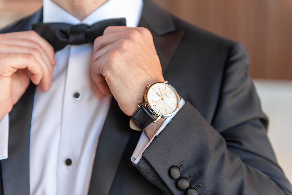 Groom getting ready for his outdoor destination wedding by adjusting his bowtie and showing off his elegant wedding watch in his charcoal gray suit coat. #groomoutfit #groomwatch #gettingreadyphotography #weddingphotography #groomshot #weddingbowtie #groomssuit #groomgettingready #zionwedding #outdoorceremony #weddingplanner #destinationwedding