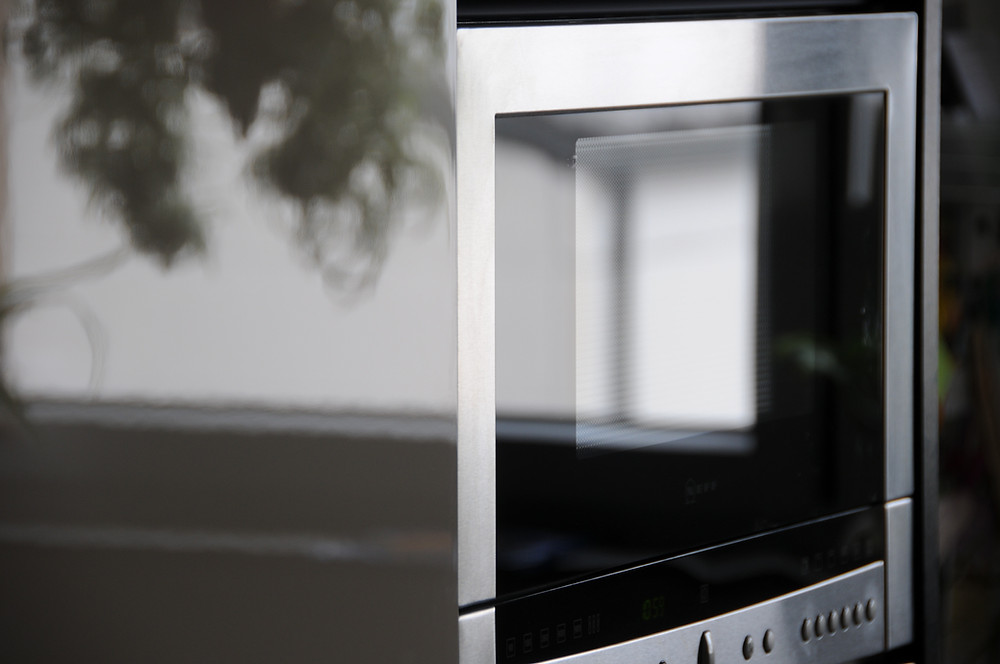 An artsy shot of a microwave, reflecting the external scene of a shadow of leaves and a window.