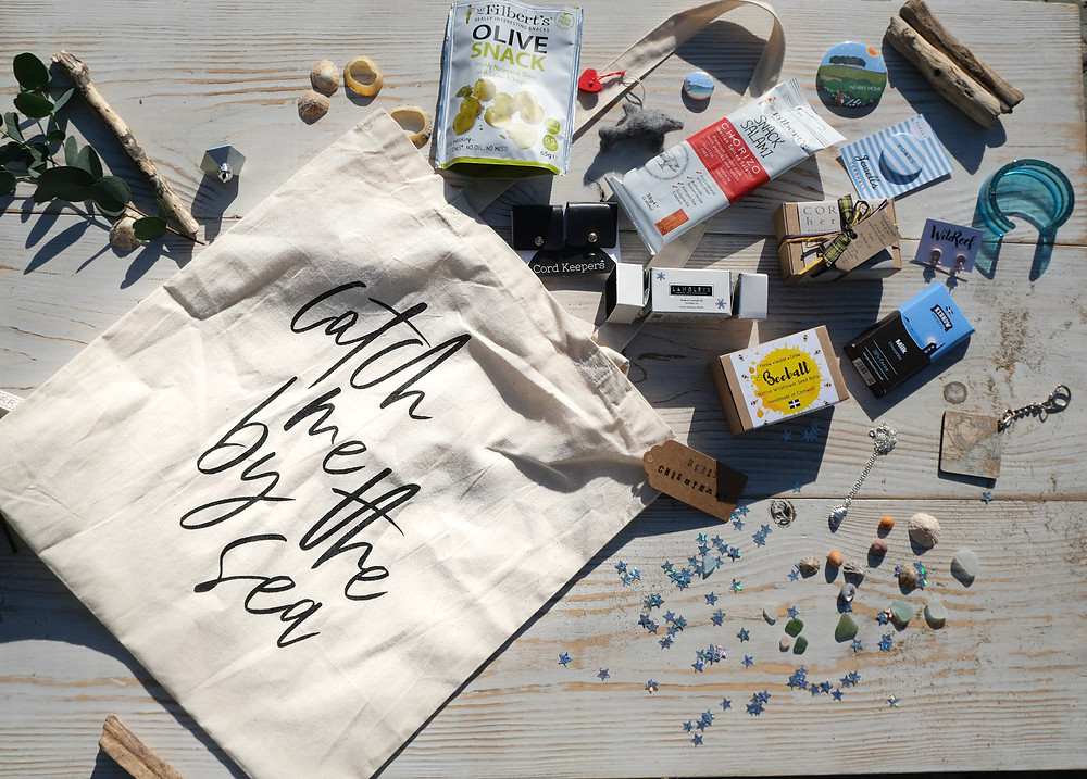 A tote bag which reads Catch Me By the Sea is exploding with gift items including chocolates, seeds, jewellery and soap