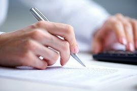 Photo of hands holding pen under documen