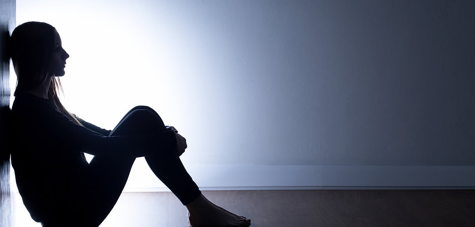 Teenager with depression sitting alone i