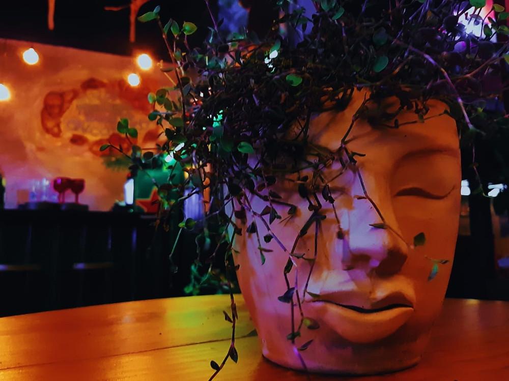 Foto mostra um vaso de barro em forma de rosto com o bar do SinsPire no fundo