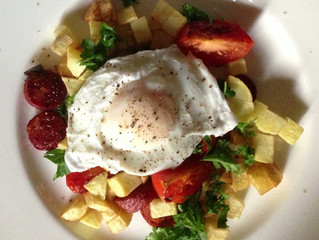 Poached egg with chorize, potato and tomato