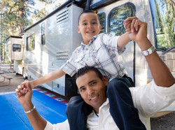 Happy Hispanic Father and Son In Front of Their Beautiful RV At The Campground