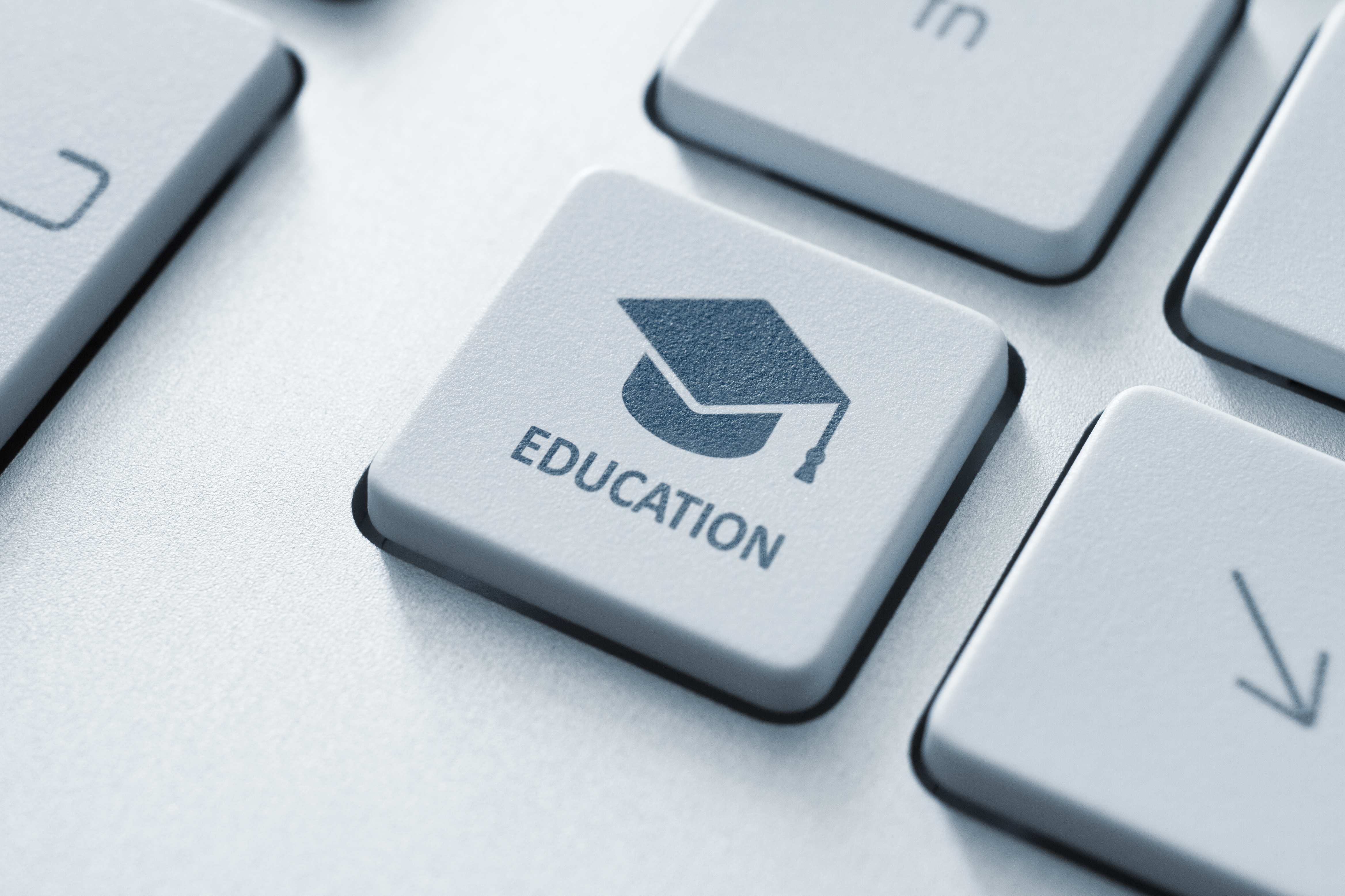 Button with graduation cap icon on a modern computer keyboard.jpg Online education concept