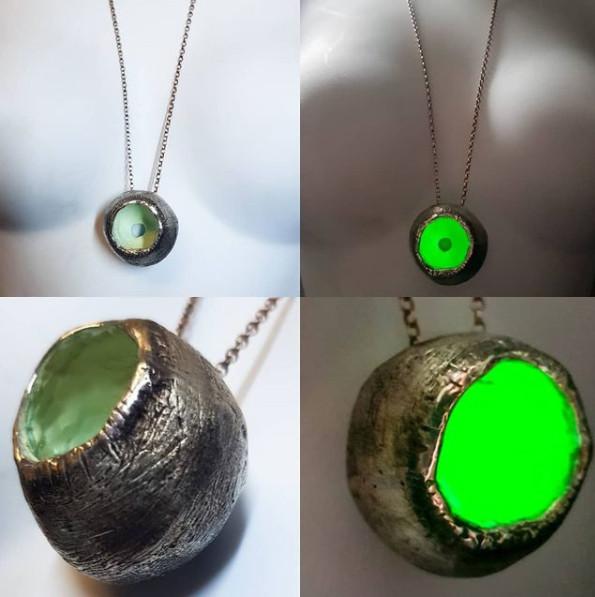 Silver gwybod pendant that has bright green glow in the dark inside