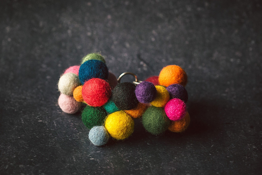 A bangle made of lots of differently coloured small felt balls