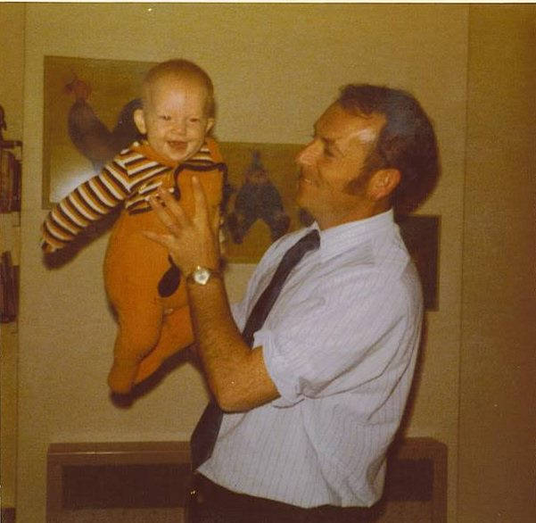 Baby Lydia in 1974 dressed in babygrow being held by a very cheerful dad with mahoosive sideburns