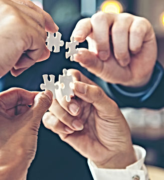 Four hands connecting four jigsaw pieces together