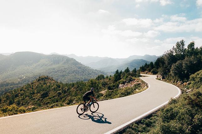cyclist-riding-bike-sunset-mountain-road