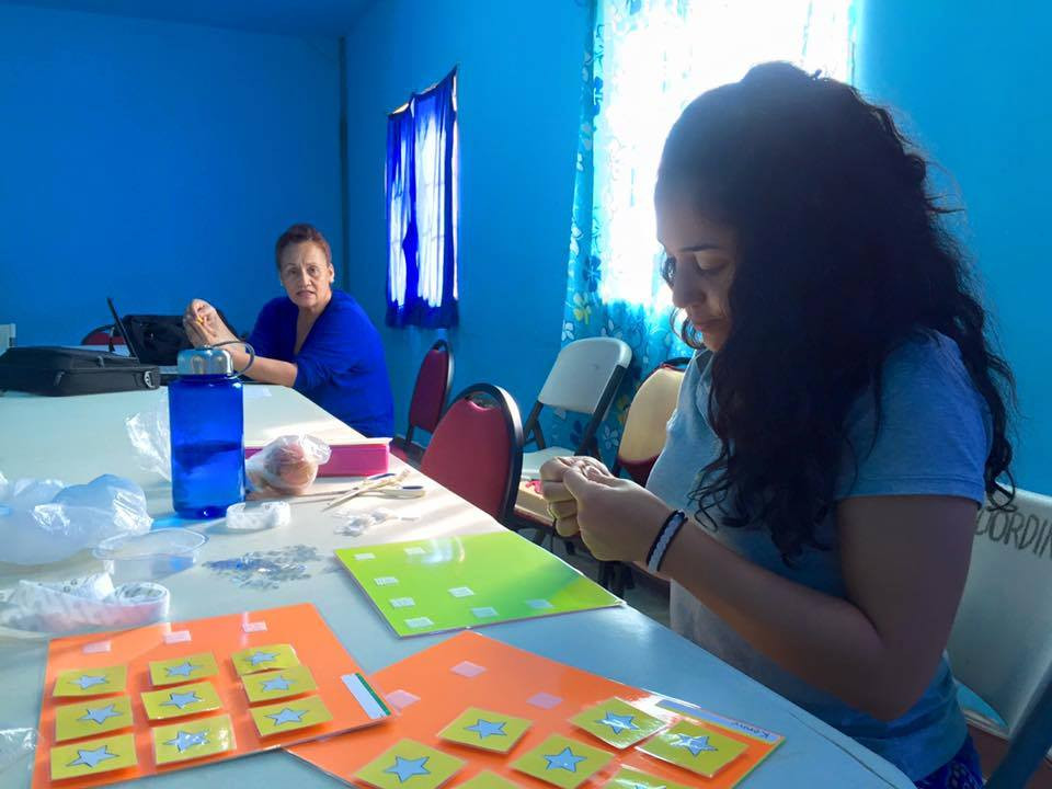 Volunteer Ruthie Holmes prepares token boards which are used to help children with behavior problems. She helped present these in a Special Education workshop for the Department of Education, Kolonia, Pohnpei.