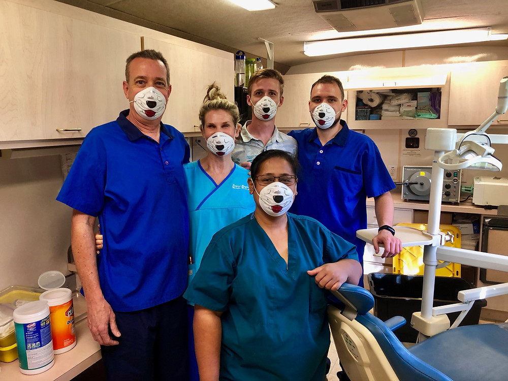 Dr. Jim (left) with wife Nicole and sons Matt and Tom works in our mobile dental clinic with local dental assistant Yumi