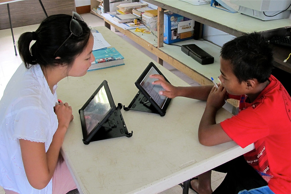 April teaches English to a student using iPad tablet computers.