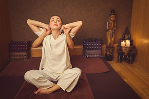 Calm girl stretching her body with masseur.jpg