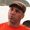 Tata Euandilo homem branco trajando camisa laranja e boina marrom