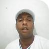 Ogan Canarinho homem negro de camisa e boné branco
