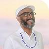 Perfil do Tata Kasulembe homem negro de barba óculos trajando roupa e boina branca