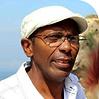 Tata Jitu homem negro de óculos trajando roupa e boina branca