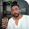 Tata Kisanje homem branco de barba preta trajando camisa branca