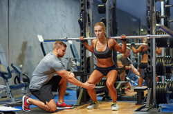 sport, fitness, teamwork, bodybuilding and people concept - young woman and personal trainer with ba