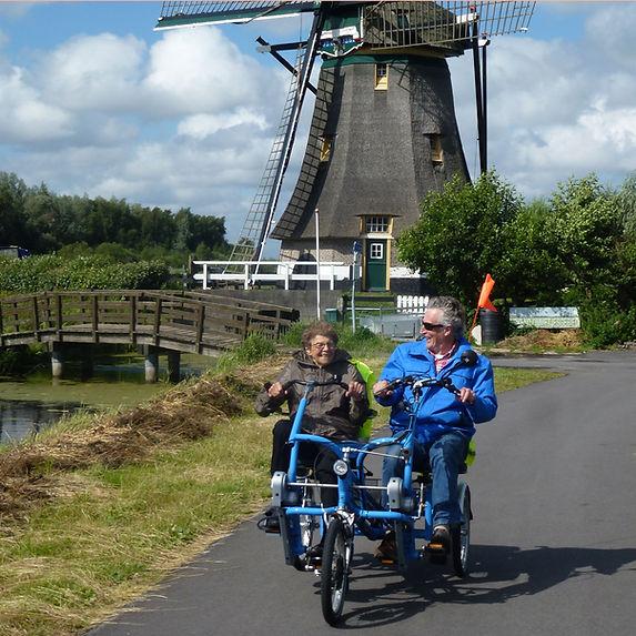 Fietsmaatje met vrijwilliger op duo fiets voor een molen