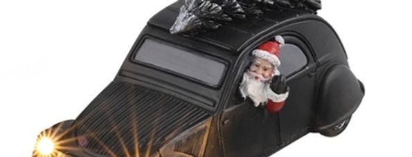 Mellem metal bil med julemand, juletræ og led lys.