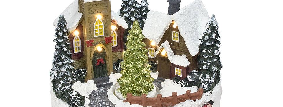 Lille by med hus, kirke og juletræ som køre rundt